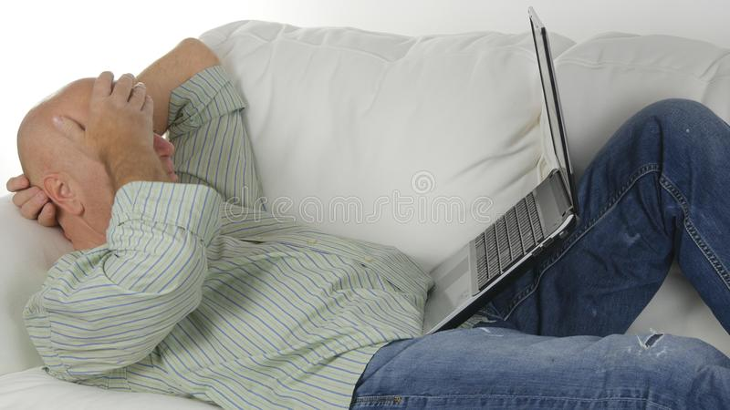 停留在生活的长沙发和工作的轻松的商人使用膝上型计算机 免版税库存照片