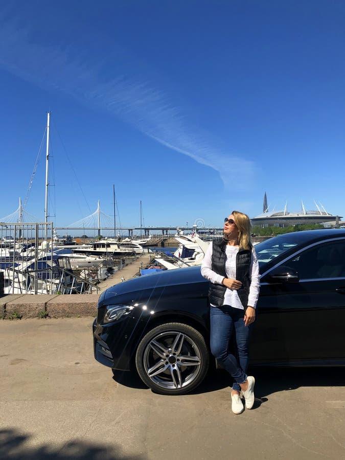 停留在豪华黑附近的妇女停车场在海洋的游艇附近 图库摄影