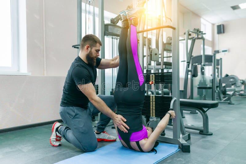 做与个人辅导员的年轻女人修复锻炼使用kinesi机器,健身健身房背景 不随意运动 库存照片