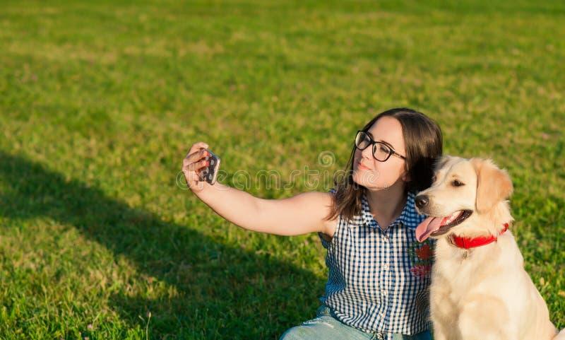 做与她的狗的年轻女人画象selfie 免版税库存图片