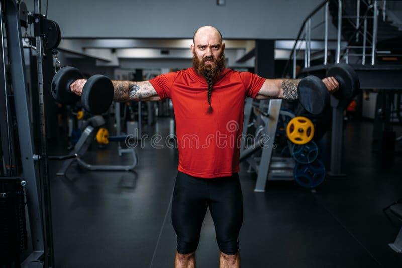 做与哑铃的举重运动员锻炼在健身房 库存图片