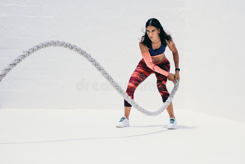 做健身锻炼的妇女使用争斗绳索 免版税库存图片