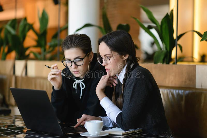 做家庭作业的女小学生使用膝上型计算机 图库摄影