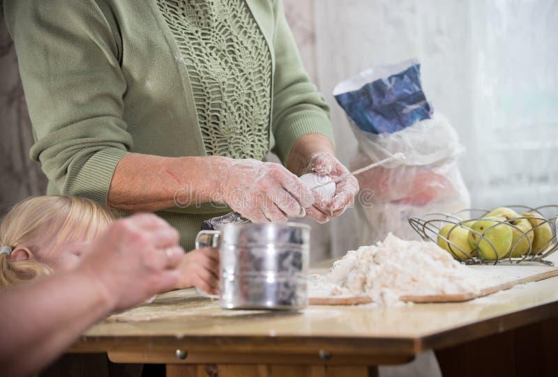 做小的饼的一个老妇人 做面团在书桌 拿着鸡蛋 库存照片
