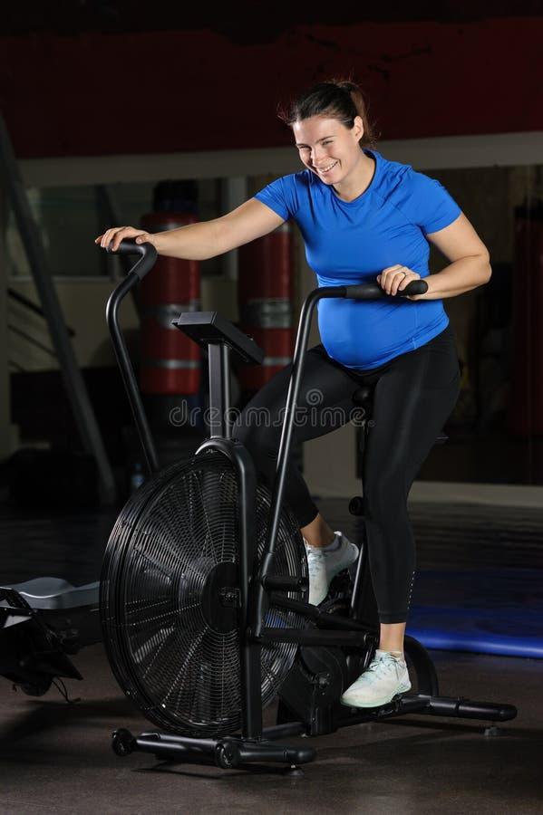 做强烈的锻炼的孕妇在健身房空气自行车 免版税库存照片