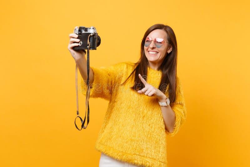做心脏的玻璃的微笑的年轻女人采取在减速火箭的葡萄酒照片照相机射击的selfie,指向食指 免版税库存照片