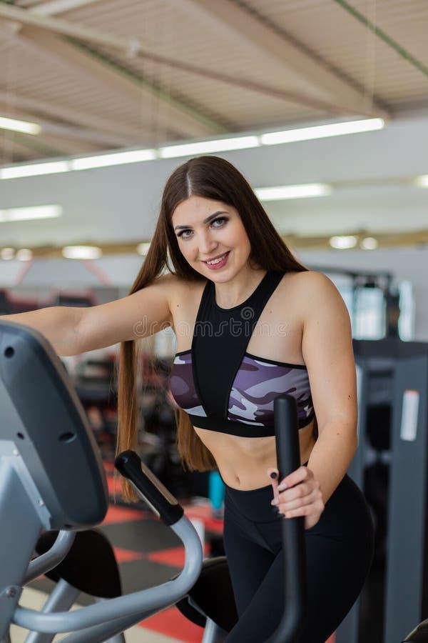 做在健身房侧视图的运动女孩一个椭球 在椭球的妇女火车 体育运动和健康生活方式概念 免版税库存图片