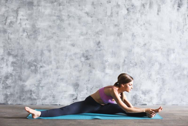 做在瑜伽席子的运动服的妇女伸展运动在健身房 图库摄影