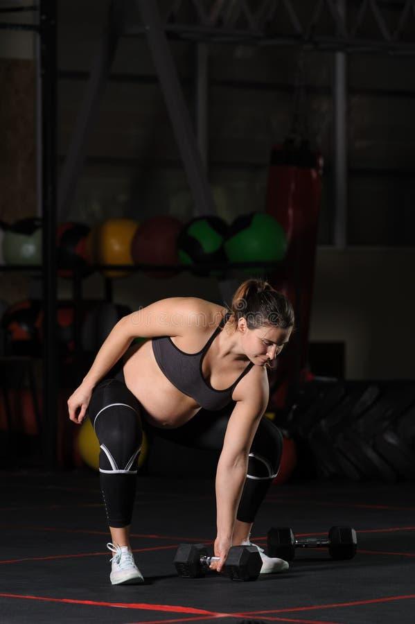 做哑铃力量夺取的怀孕的女运动员 库存图片