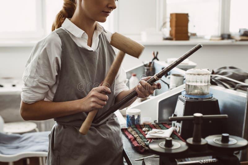 做正确的大小 弯曲在路的女性首饰设计师侧视图银色空白使用短槌锤子 图库摄影