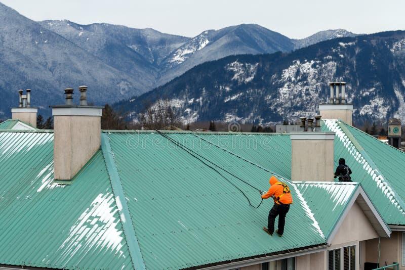 做某一维护和紧急修理的建筑工人在冬天风暴以后 免版税库存照片