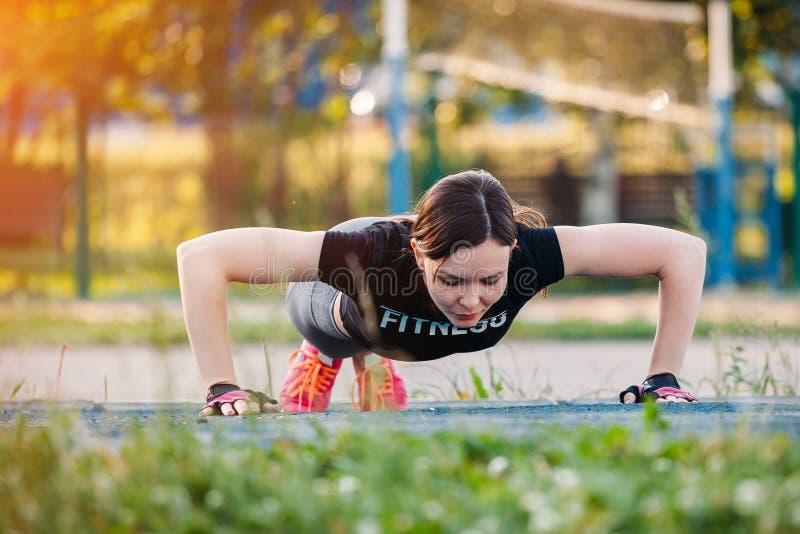 做有些俯卧撑的美丽的亭亭玉立的浅黑肤色的男人外部在公园 在室外交叉训练锻炼期间的健身妇女 免版税库存照片