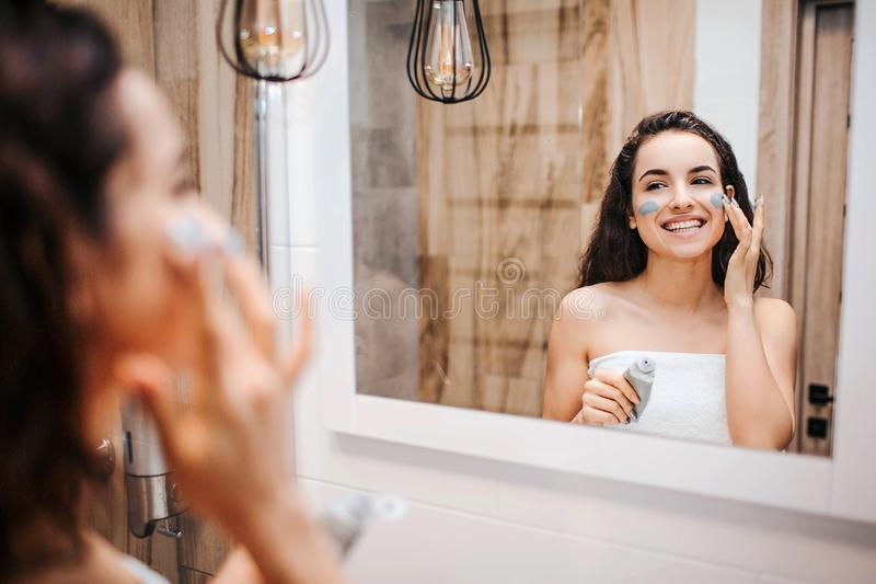 做早晨晚上惯例的年轻运动的深色头发的美女在镜子 她使用面膜和微笑 机体 库存照片