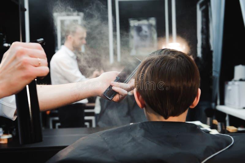做理发的年轻英俊的理发师逗人喜爱的男孩在理发店 免版税库存图片
