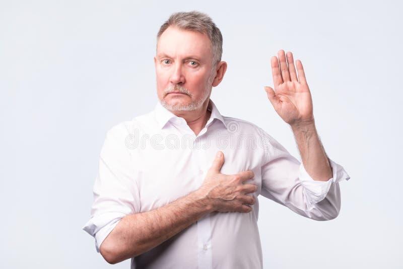做誓言的白色衬衫的英俊的老人 给一个诺言 库存图片