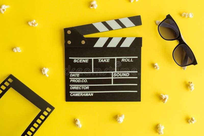 做背景的戏院和电影 与3d玻璃、在黄色隔绝的框架以影片小条的形式和玉米花的Clapperboard 免版税库存图片