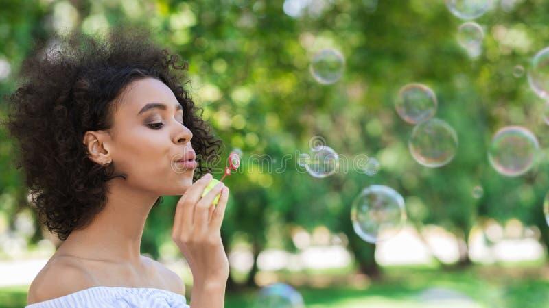做肥皂泡的年轻美女画象 免版税库存照片