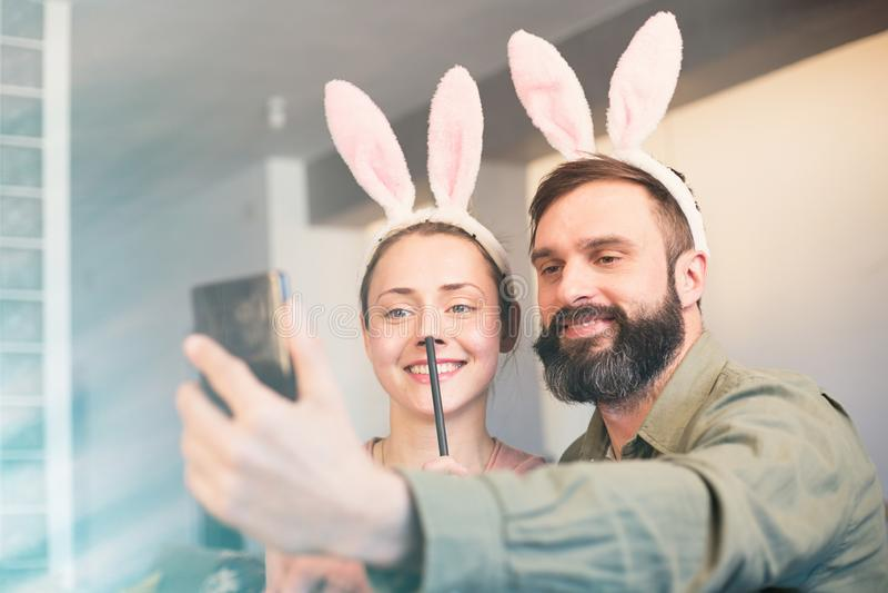 做selfie的年轻爱恋的夫妇在有桃红色兔子耳朵的手机头的 愉快的家庭为复活节做准备 免版税图库摄影