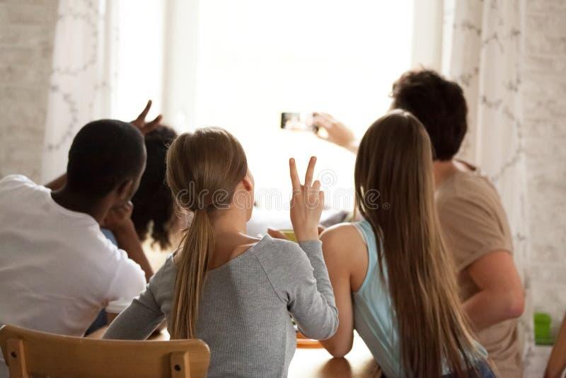 做selfie,记录的录影的背面图愉快的多种族朋友 免版税库存照片