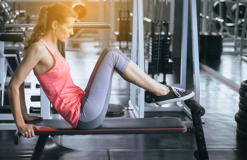 做situp或咬嚼在健身房的年轻女人,肌肉女性的锻炼她的胃 免版税库存照片