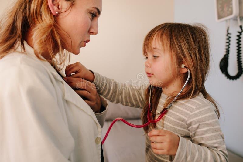 假装对医生的女孩审查她的儿科医生 库存图片