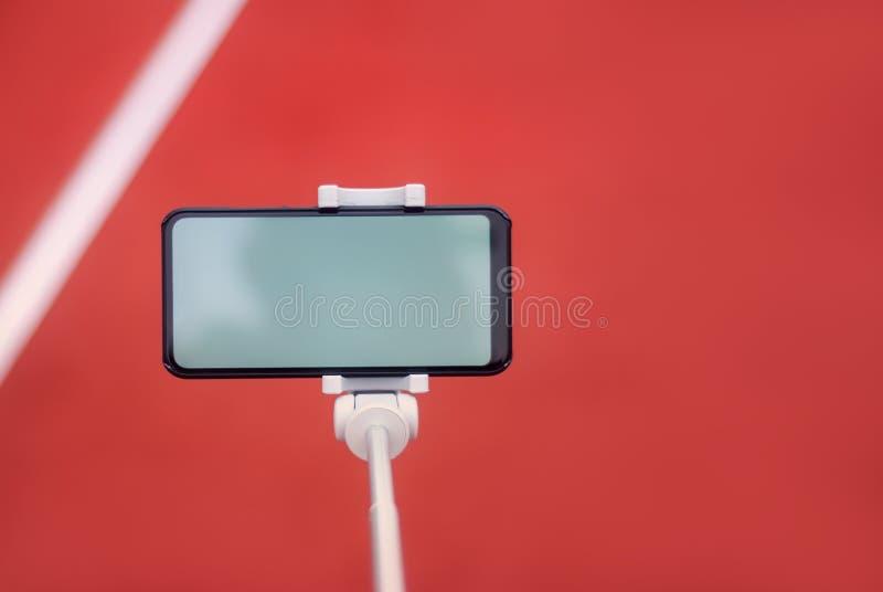 假装有一个三脚架的一个黑智能手机在红色轨道的背景跑和体育体育场的 免版税图库摄影