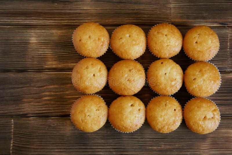 十二块可口金黄杯形蛋糕说谎杉木板条木表面上  鲜美和健康食物 白天 库存图片