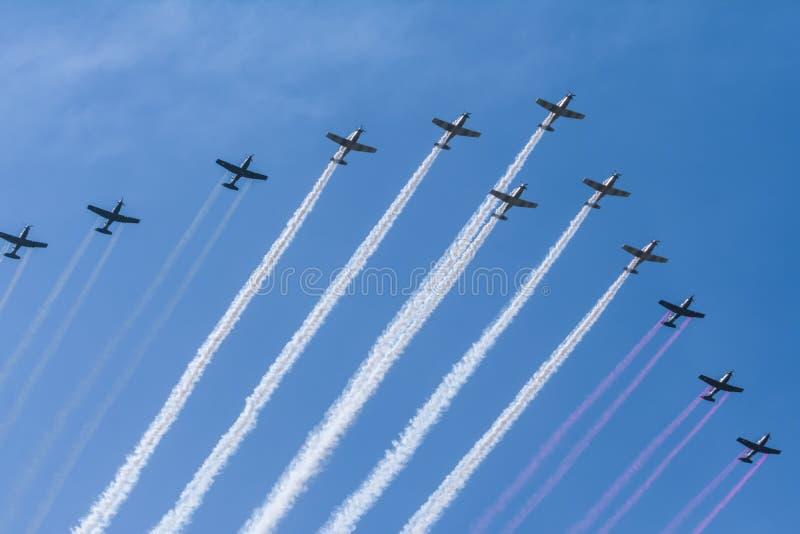十二架特技飞机是散发绿色,白色和红色烟 库存照片