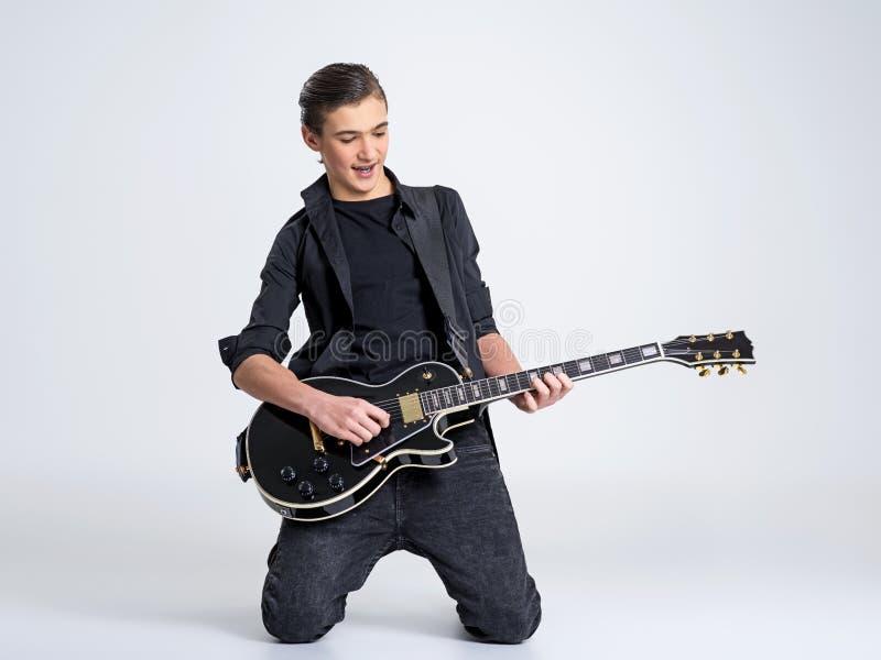 十五岁有一把黑电吉他的吉他弹奏者 少年音乐家拿着吉他 免版税图库摄影