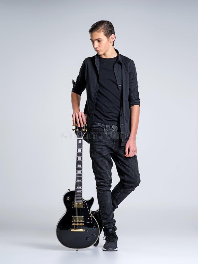 十五岁有一把黑电吉他的吉他弹奏者 免版税库存照片
