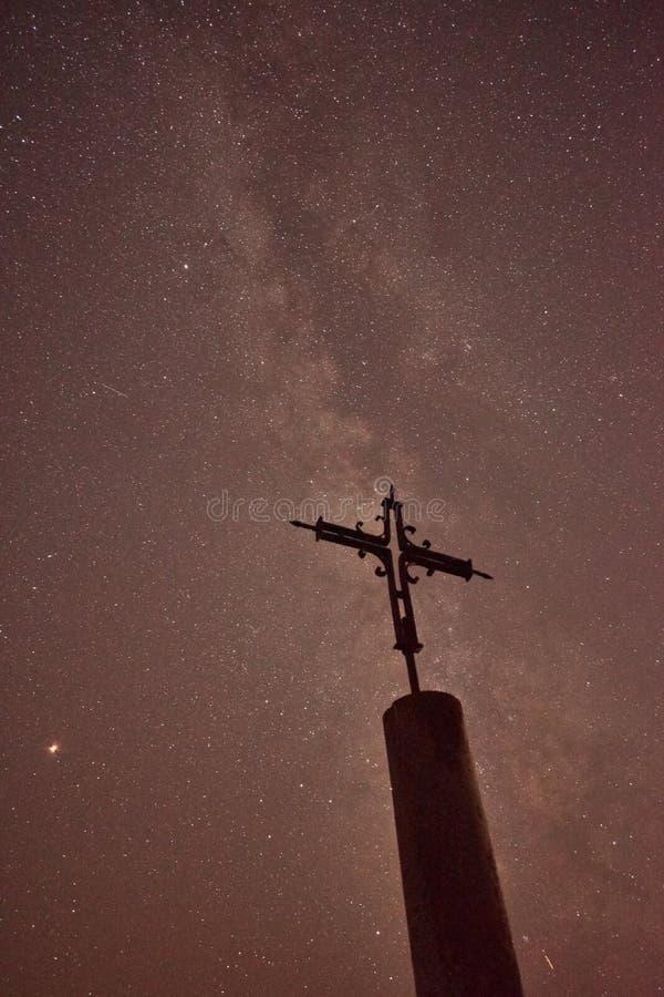 十字架剪影在晚上有美好的银河背景 免版税库存图片