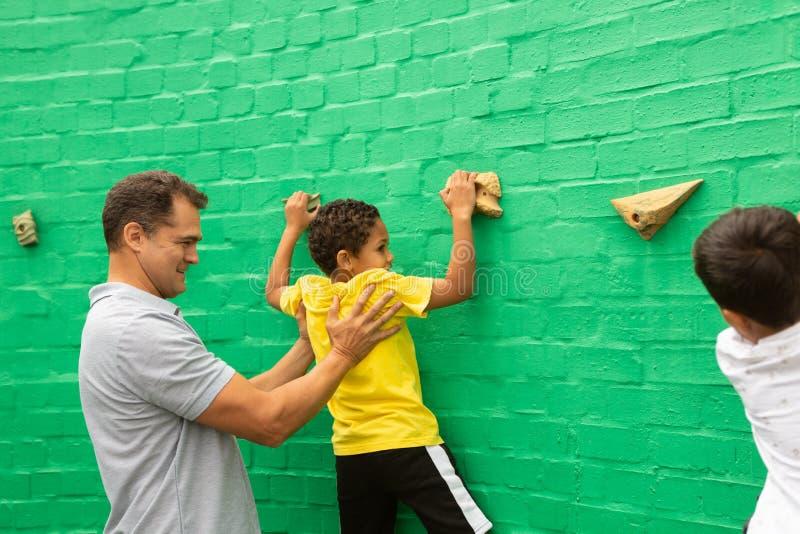 协助男小学生的男老师攀登人为墙壁 免版税库存图片