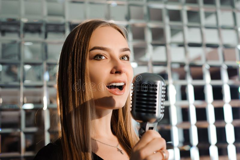 卡拉OK演唱党 有话筒唱歌的秀丽女孩 迪斯科女孩当事人红色 庆祝 库存照片