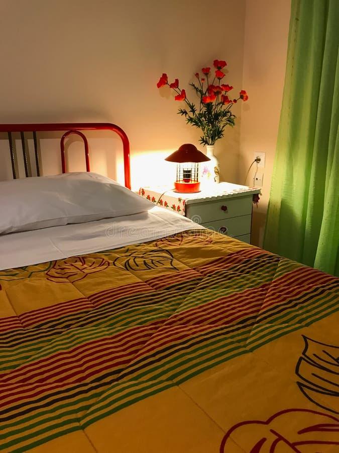 卧室的充满活力的色的内部 枕头和五颜六色的床罩在床上 卧室室内设计 免版税库存图片