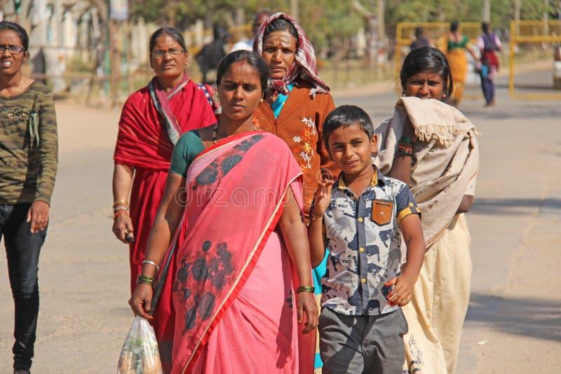 印度,亨比,2018年2月2日 一群人、男人和妇女莎丽服的,步行沿亨比村庄街道  亨比, 免版税图库摄影