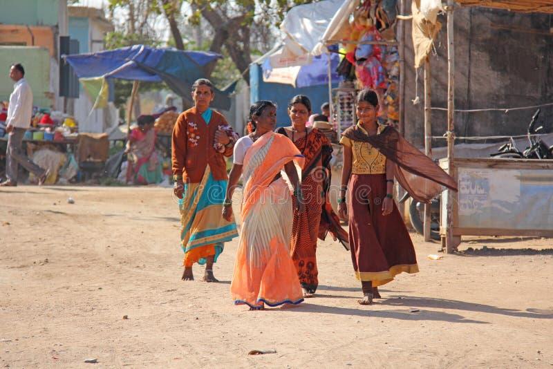 印度,亨比, 2018年2月02日 明亮的莎丽服的妇女步行沿着向下街道和微笑 印第安妇女 库存照片