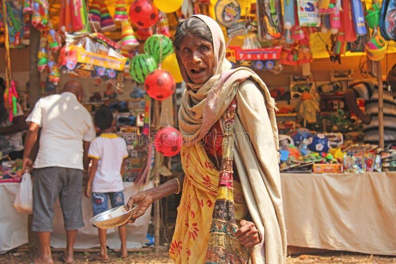 印度,果阿,2018年1月28日 可怜的妇女请求在街道上的金钱在印度 一名叫化子妇女用一只被伸出的手 贫穷 免版税图库摄影