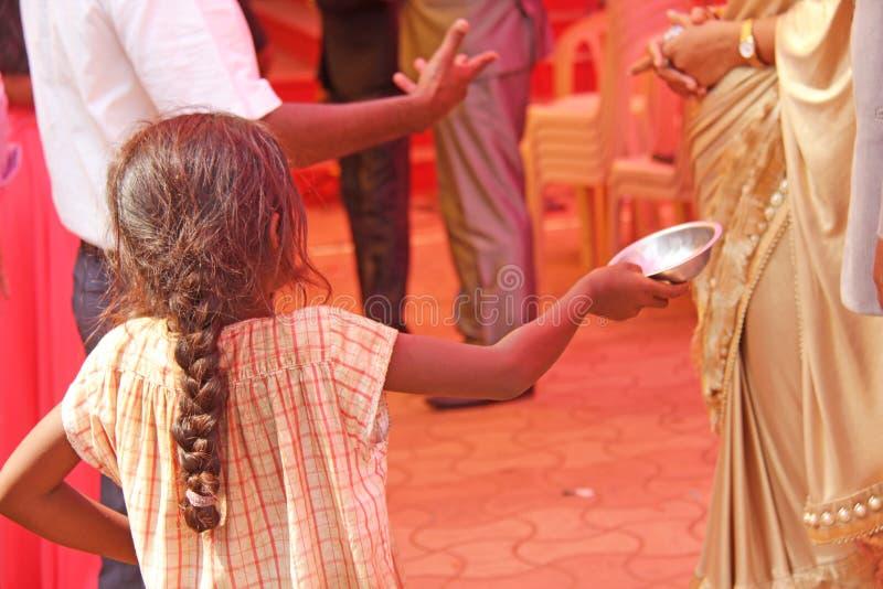 印度,果阿,2018年1月28日 可怜的孩子要求从路人的金钱,孩子用被伸出的手,叫化子 印度贫穷 图库摄影