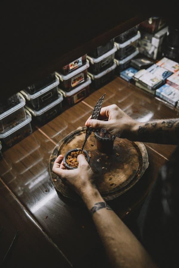 卷起水烟筒的一个人的特写镜头入果酱 免版税库存图片