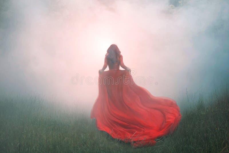 华美的惊人的美妙的有长的飞行波列的,有红色卷发奔跑的一个神奇女孩猩红色红色礼服 免版税库存照片