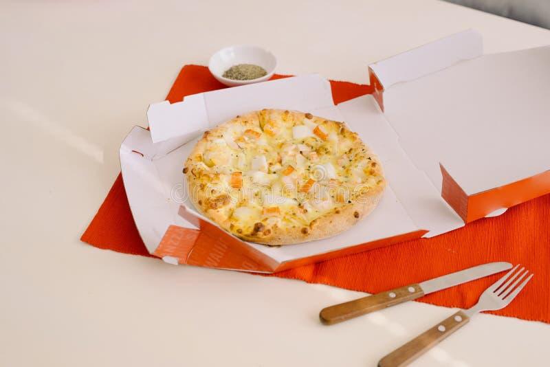 午饭时间,在一个开放箱子的比萨在桌上 库存图片