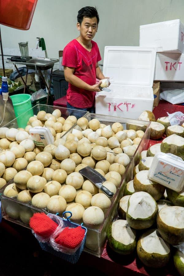 卖新鲜的年轻椰子的供营商在一家街道商店在中国镇在新加坡 免版税库存照片