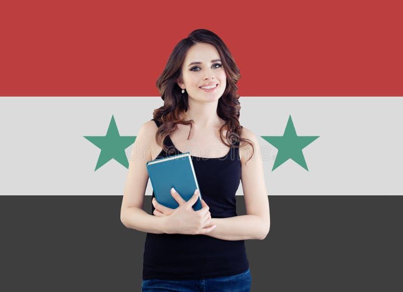 反对叙利亚旗子背景的愉快的妇女,叙利亚难民概念的新的生活 图库摄影