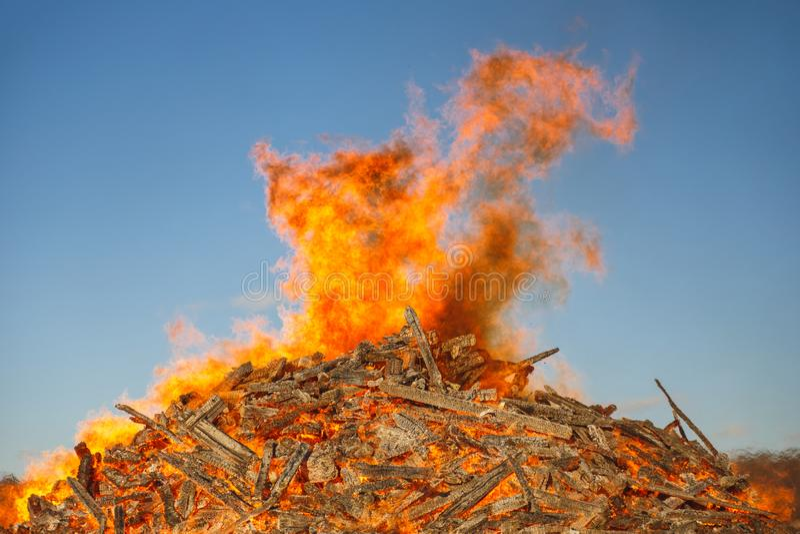 反对天空蔚蓝的燃烧的巨大的篝火 图库摄影