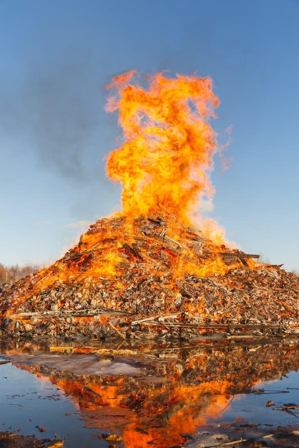 反对天空蔚蓝的燃烧的巨大的篝火 免版税库存图片