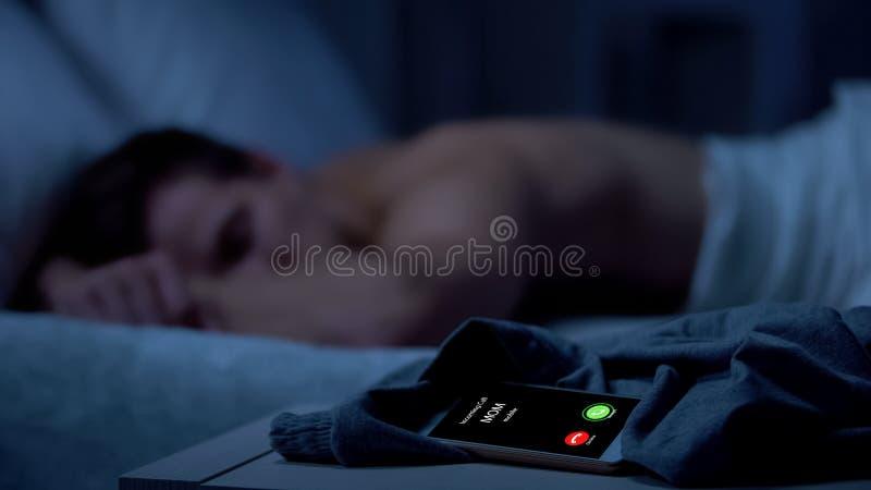 叫的妈妈,睡觉在背景,错过的电话,紧急新闻的男性 免版税库存图片