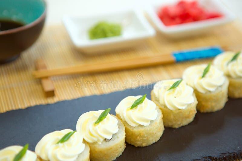 可口新鲜,天麸罗和被烘烤的寿司maki的分类与三文鱼、黄瓜、鲕梨、炒蛋、虾和unagi调味汁 免版税库存图片