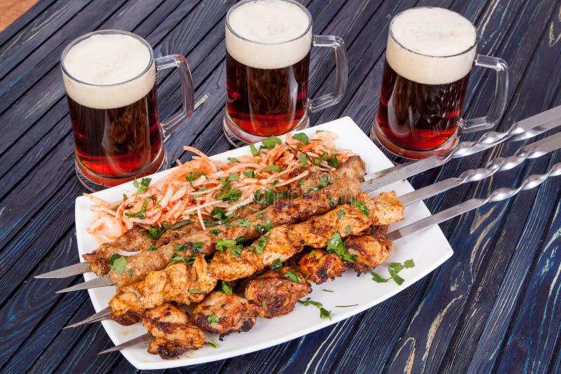 可口烤羊羔串起用在桌上的啤酒 库存照片