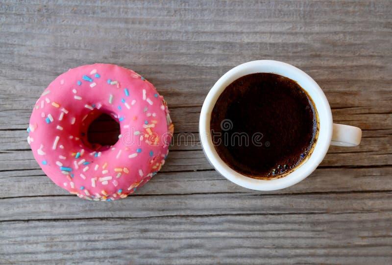 可口甜新鲜的桃红色多福饼和咖啡在老木背景的 早餐,便当,面包店概念 免版税图库摄影
