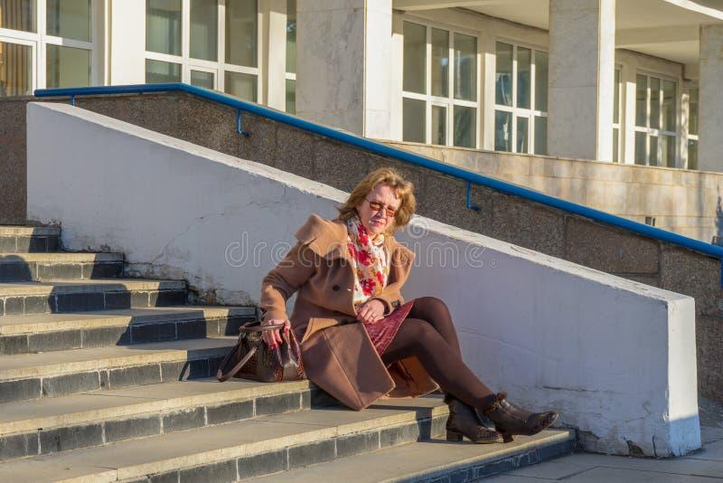 可爱的中年妇女穿时髦的外套的和鞋子与袋子坐台阶在早期的春天跨步办公楼在 免版税库存照片